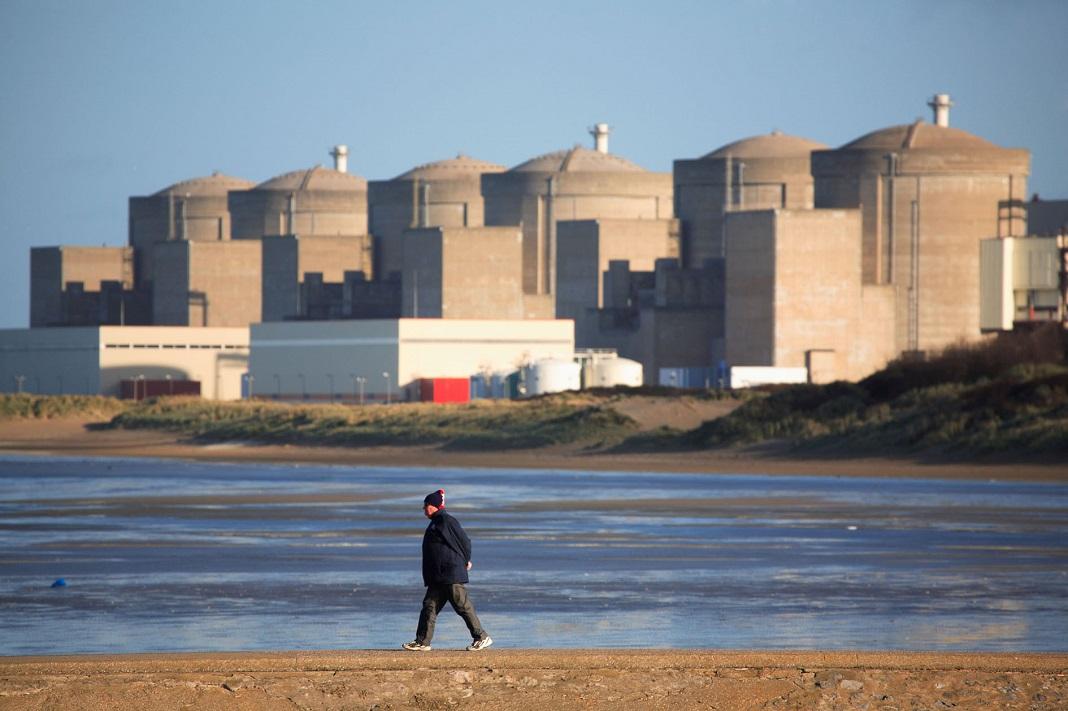 Homme se promenant sur la digue de Petit Fort Philippe devant la centrale nucléaire de Gravelines. Nord de la France. | Northern France: nuclear plant in Gravelines.