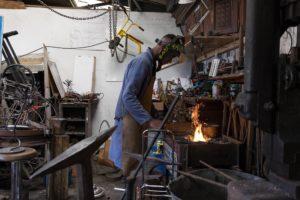 Christian apprend à forger dans l'atelier dans un artisan du quartier, en prépartation de son entrée en CAP Chaudronnerie dans un lycée technique de Saint-Nazaire à la rentrée / Photo: Armandine Penna