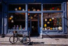 Un vélo est stationné en face d'un commerce neuf situé dans un immeuble ancien. Des abats-jour multicolores ornent la vitrine.
