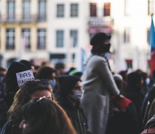 """Manifestants dans la rue à Lyon, en novembre 2020. Sur une pancarte, on lit : """"Pas d'accord""""."""